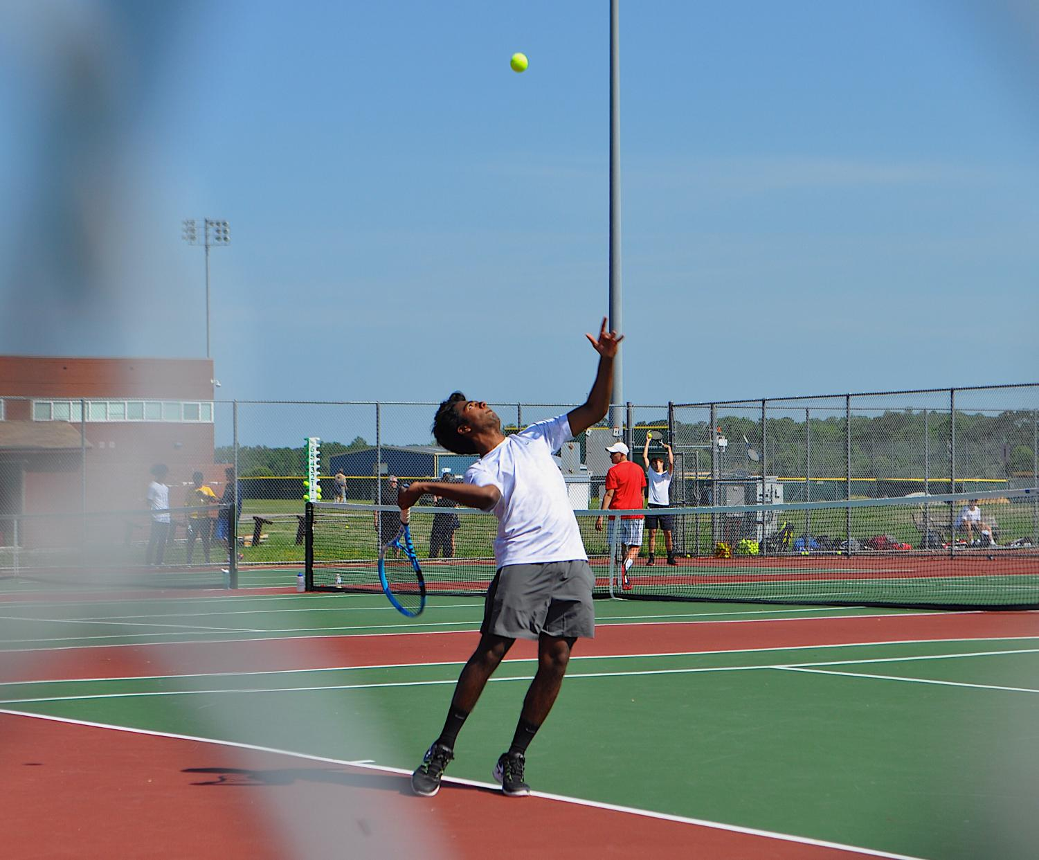 Junior Anand Kolli serves in pod game against Bayside High School. Photo by Katie Kerrigan