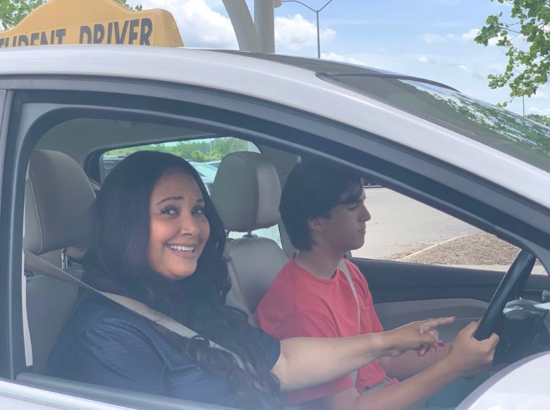 Devona Carey starts her lesson in the student parking lot with sophomore Alex Logg on May 14, 2019