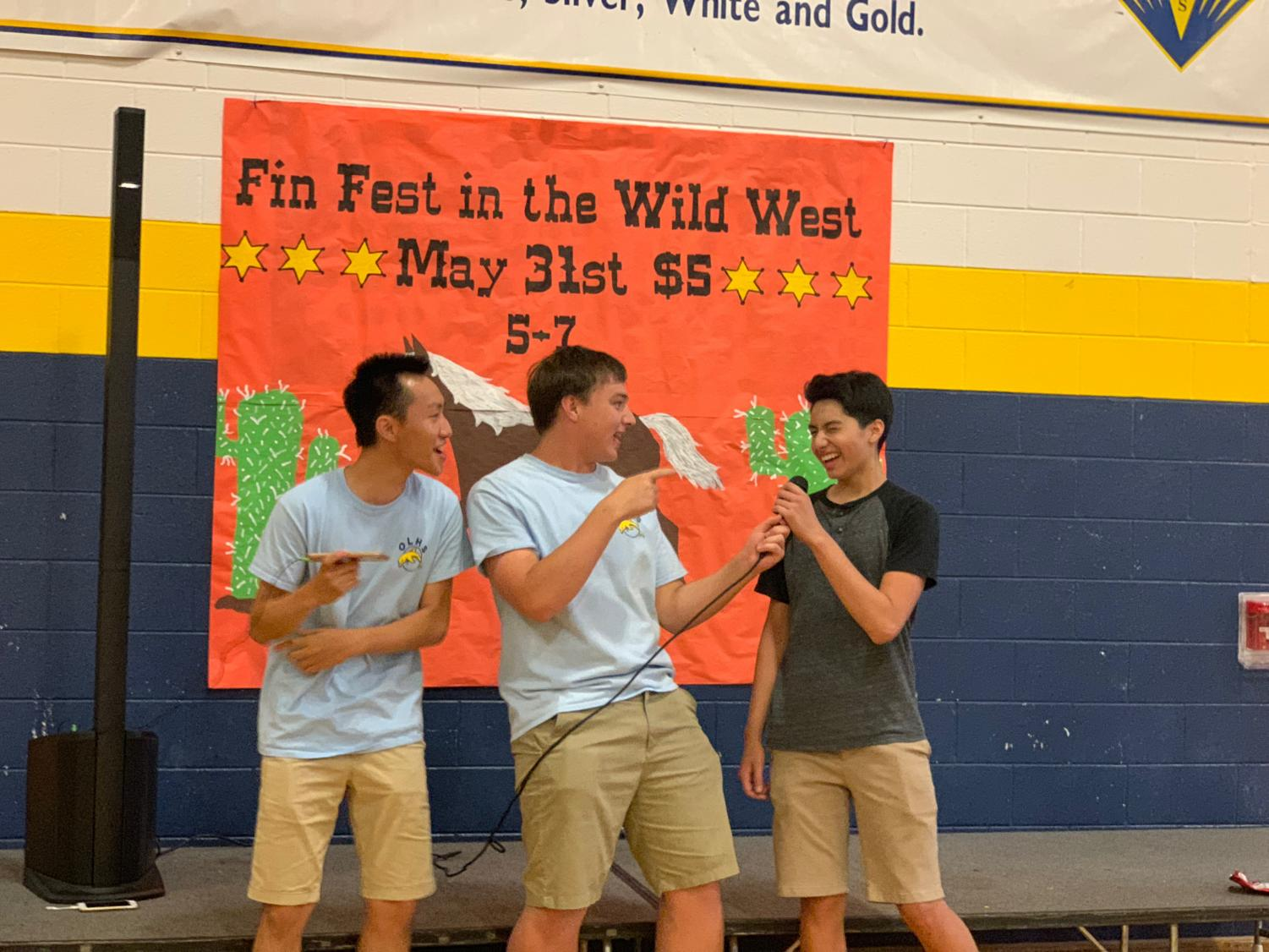 Senior John Wong, senior Lars Wirstrom, and sophomore Josh Esposo sing karaoke on the Fin Fest stage on May 31 in the gymnasium.
