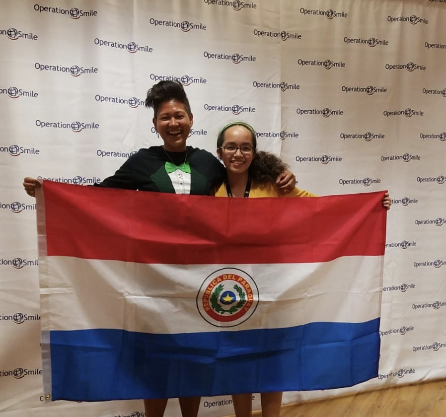 Workshop attendee Sophia Libonate and chaperone Christabelle Fernandez present the Paraguay flag after learning the location of their upcoming mission.