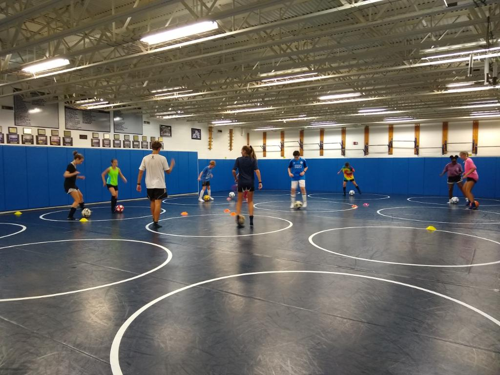 Both volunteers and campers practice their footwork skills in the Ocean Lakes wrestling room on July 23.