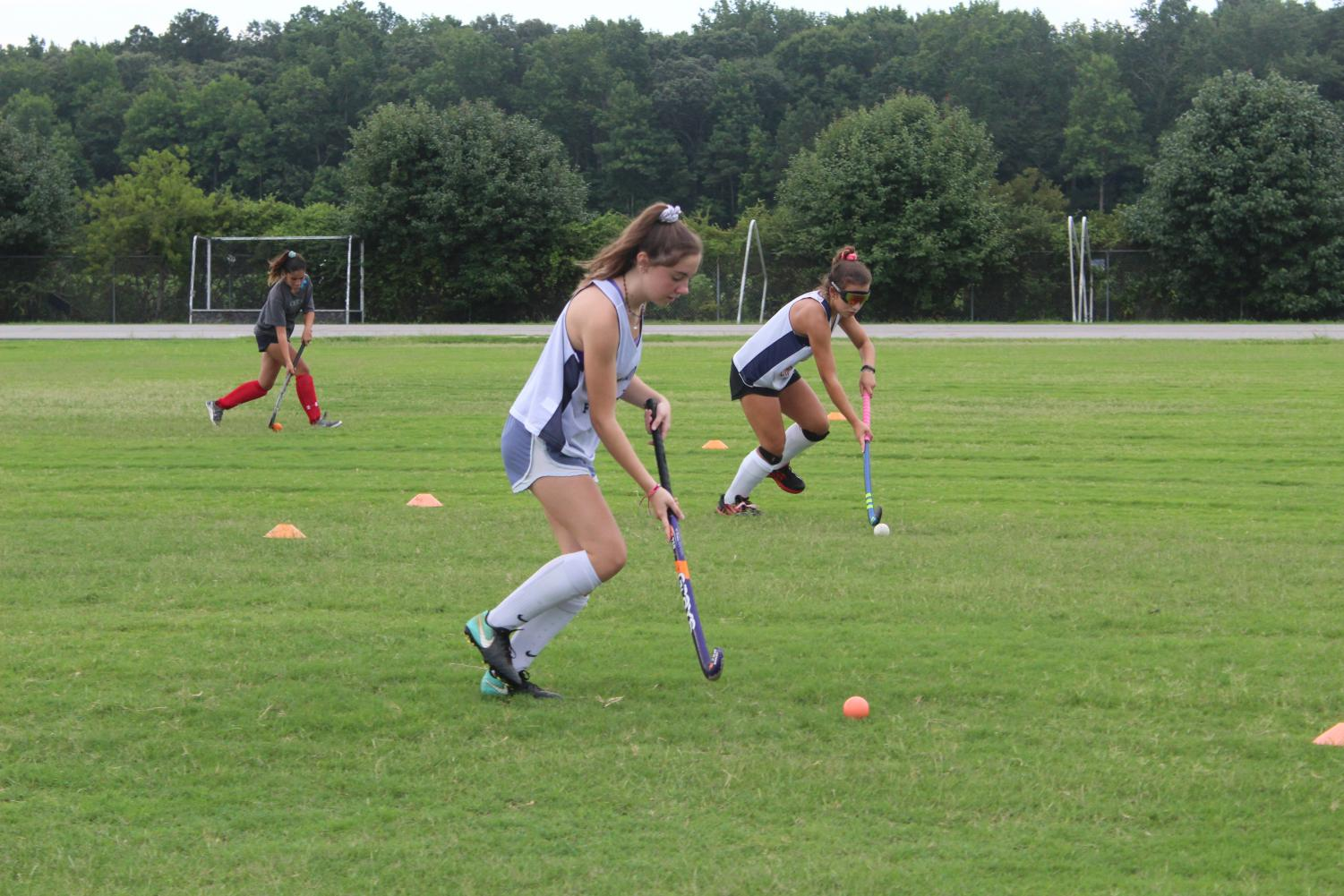 Junior Kelly McCarty and sophomore Kaitlyn Hertz dribble the ball during a conditioning drill on July 19.