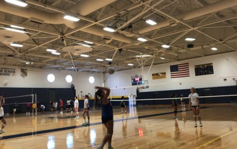 Ally Zongolowicz serves a volleyball on the new gym floors.