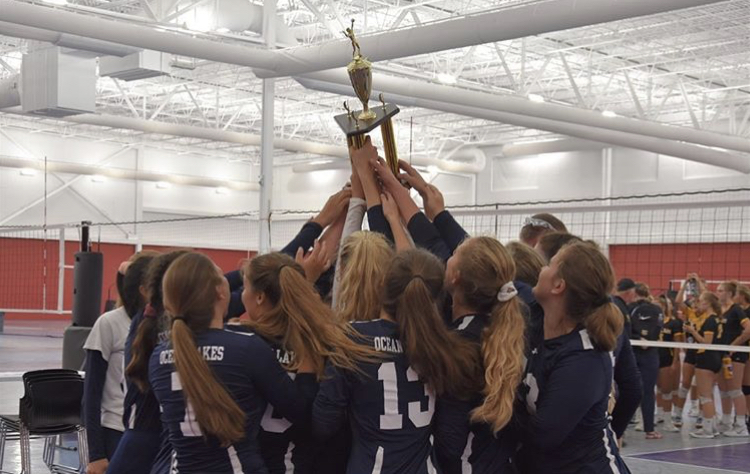 The girls volleyball team hold up their tournament trophy shortly after their victory over Kellam on Aug. 31, 2019.