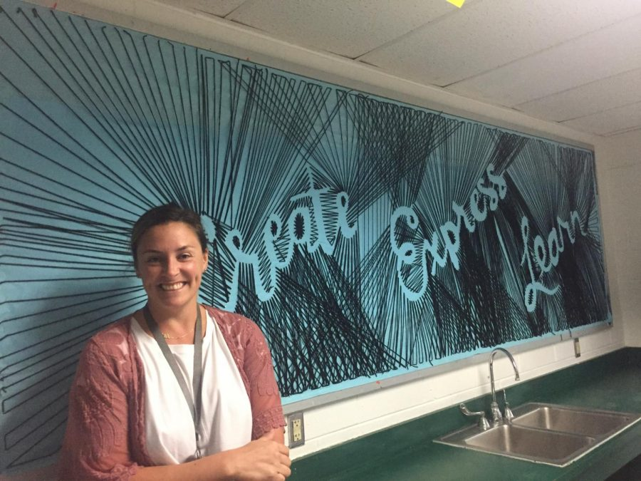 Lindsey Roberts, art teacher, sits in front of her award-winning bulletin board on the third day of school.