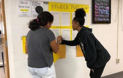 Andrea Granada and Aliyah Webster sign up to compete in powderpuff outside of room 159.