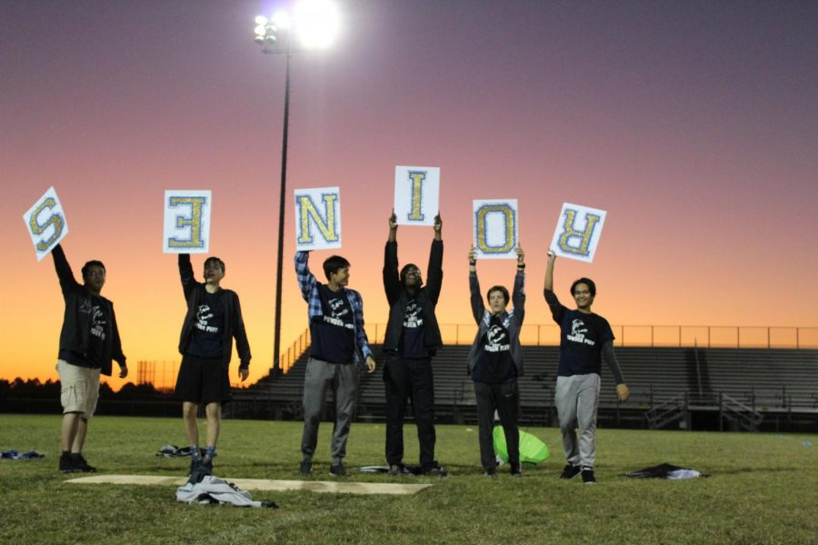The+senior+cheerleading+team+holds+up+a+sign+that+spells+out+%22SENIOR%22+on+Oct.+23.