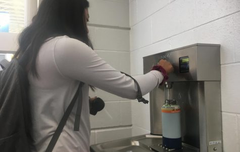 Junior Nina Dao refills Hydroflask using Elkay water fountain, located in the cafeteria foyer.