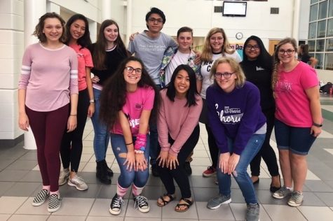 A cappella club poses for group picture in the gym foyer after performing at the girls' pink out volleyball game on Oct. 29.
