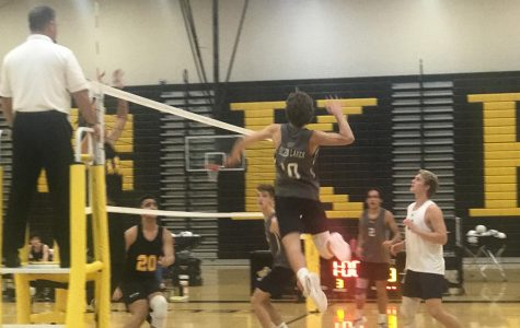 Noah Naas goes up to spike the ball after a set from Lucas Bushey.