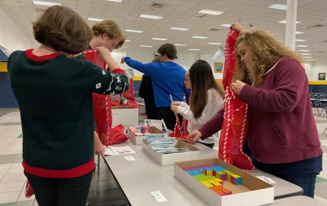 National Honor Society members stuff stockings for children in need at the winter social in the cafeteria. This article was published in modified form for the Stall Seat Journal.