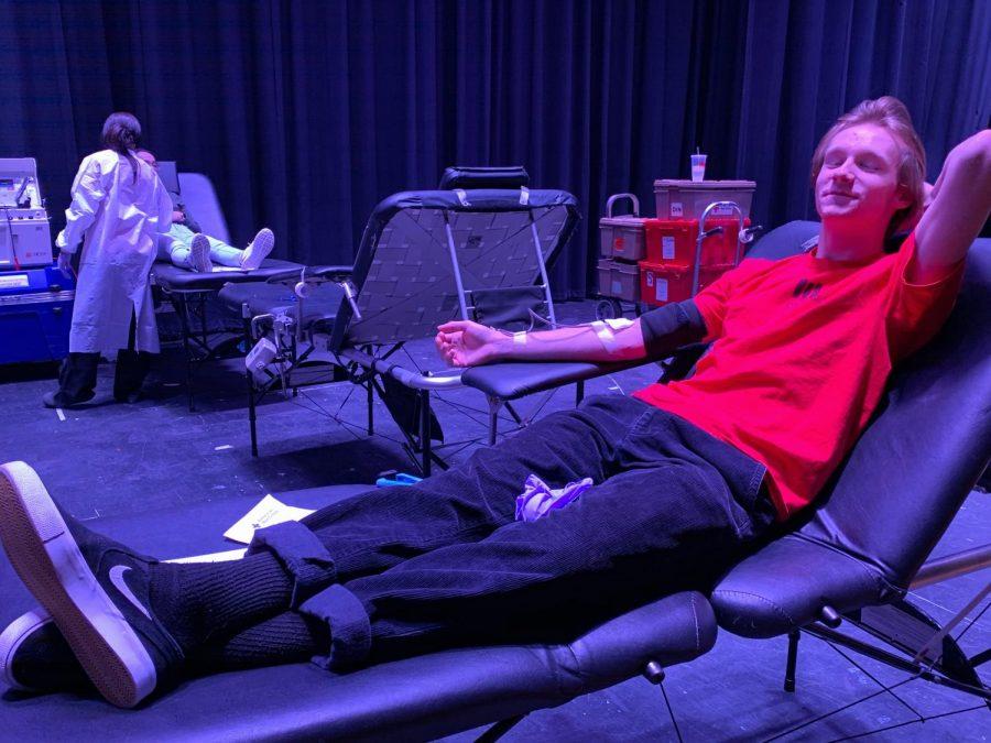 Senior Noah Wright lays on exam seat in auditorium on Dec. 12.