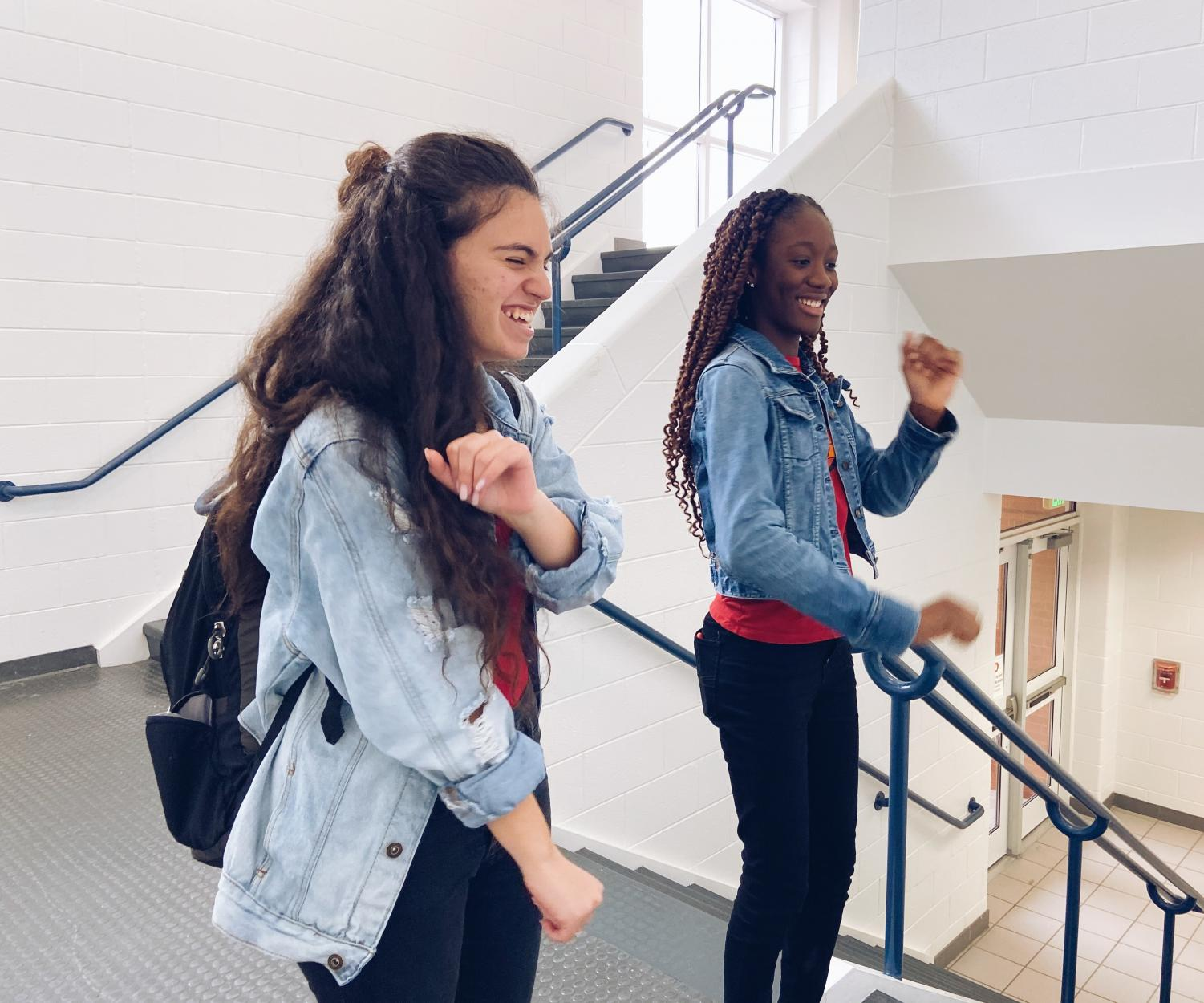 """In the stairway, sophomores Leiale Demant and Amba May-Parker dance to """"Renegade"""" for a TikTok on Dec. 12. Photo by Abby Asimos."""