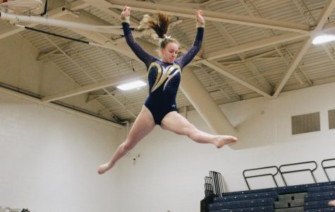 Senior Shannon McLaughlin leaps on the balance beam in the gymnasium on Dec. 12.