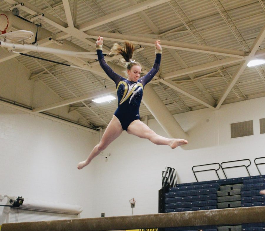 Senior+Shannon+McLaughlin+leaps+on+the+balance+beam+in+the+gymnasium+on+Dec.+12.+