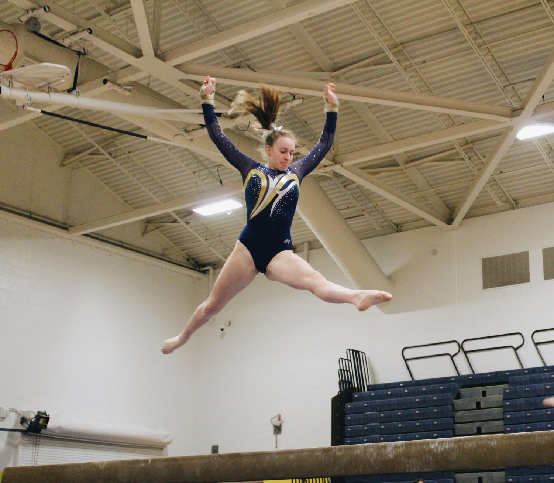 Senior Shannon McLaughlin leaps on the balance beam in the gymnasium on Dec. 12.