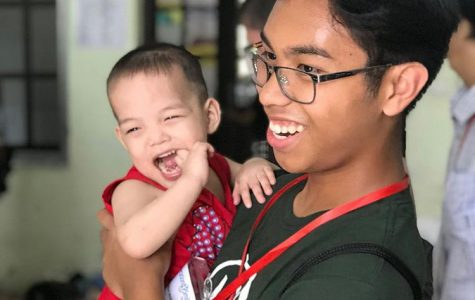 Jondre Macaraeg smiles with a baby at an orphanage during an Operation Smile trip to Vietnam in 2019.