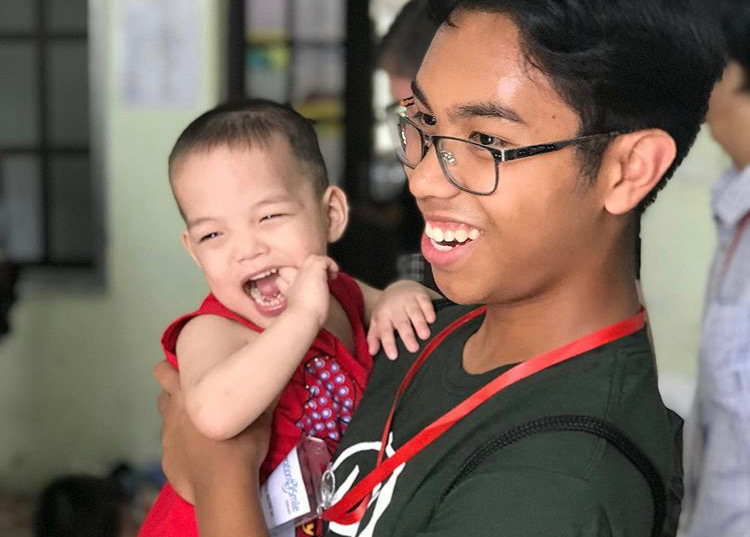Jondre+Macaraeg+smiles+with+a+baby+at+an+orphanage+during+an+Operation+Smile+trip+to+Vietnam+in+2019.