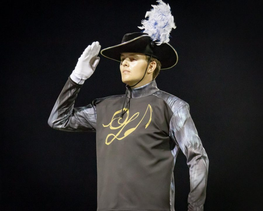 Kaden Bock acknowledges the audience with a salute before the band's performance at a home varsity football game.