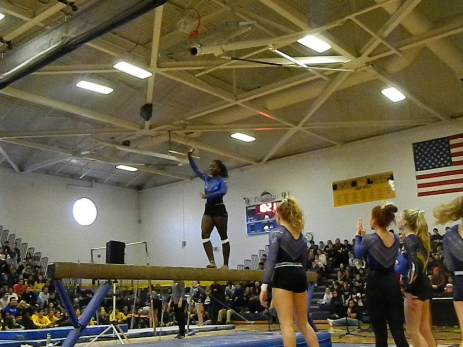 Senior Autumn Torian completes a trick on the balance beam during winter assembly. Picture taken in the school gym on Dec. 18.