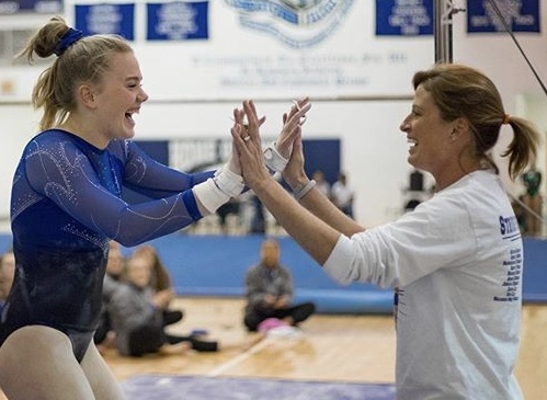 Sam Lee, sophomore, celebrates with coach Jennifer Ramey after a successful gymnastics meet.