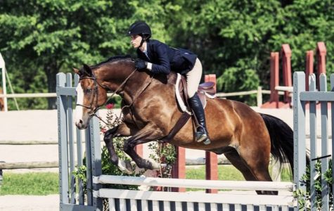 Senior Brandi Schryer and her horse jump over an obstacle at the VHSA Show in 2017.