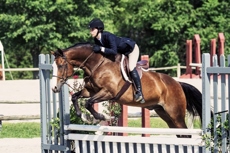 Senior+Brandi+Schryer+and+her+horse+jump+over+an+obstacle+at+the+VHSA+Show+in+2017.