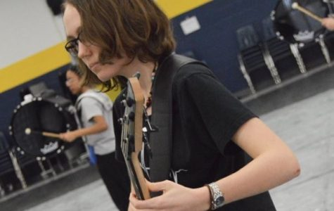 """Rachel Owen performed on bass guitar in the cafeteria for the OLIPE (Ocean Lakes Indoor Percussion Ensemble) production, """"Awaken."""""""