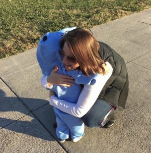 Carlin Conaway hugs the son of English teacher, Katie Anderson. Lane Anderson is dressed up as a dolphin for the 2019 Fall Fest.