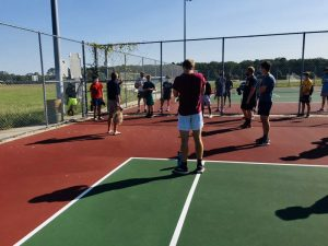Wrestling team meets on tennis courts this fall and practices social distancing during conditioning.