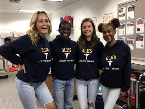 Trainers Kacey Counts, Jalen Powell, Emily Dixon, and Izzy Carter pose in the training room before a football game.