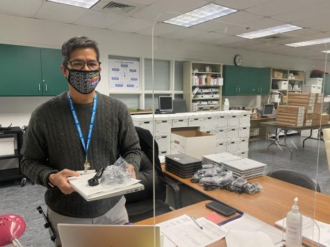 Interim IT Rome Meija distributes nearly 100 laptops as of Jan. 14, in room 101.