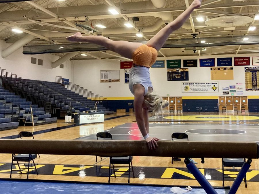 Senior Kara Lee performs a skill on the balance beam while maintaining social distance from other teammates on Jan. 19.