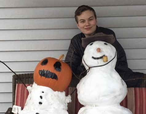 Even though students did not get a day off from virtual school, junior Tim Doughty poses with snowmen he built during lunch. Pumpkin head snowman was designed to look like a Minecraft snow golem.