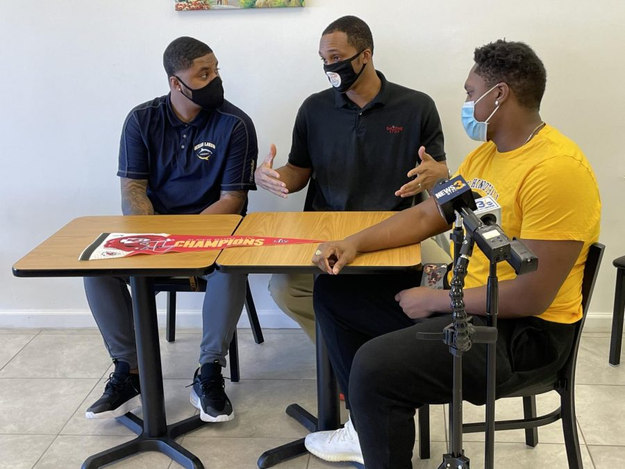 Former teammates Michael Alston, (left) and Masaddiq Walton (right) listen to Christopher Taylor (middle) share his thoughts about the appreciation event for Derrick Nnadi held at Smoothie Stop Cafe on Sat., Feb. 6.