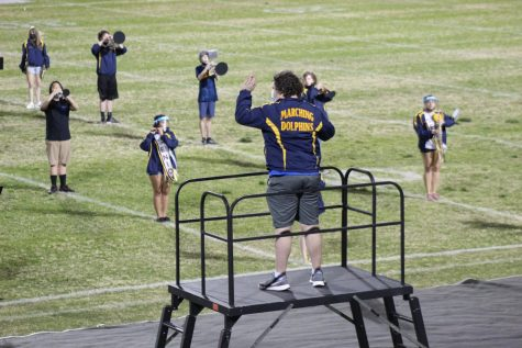 Senior Matthew Pohl leads the marching band during their performance at the senior night football game on March 26.