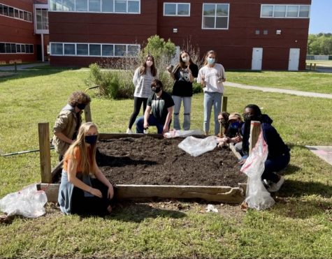 AP Environmental students finish cleaning out the flowerbed behind the cafeteria on April 22.