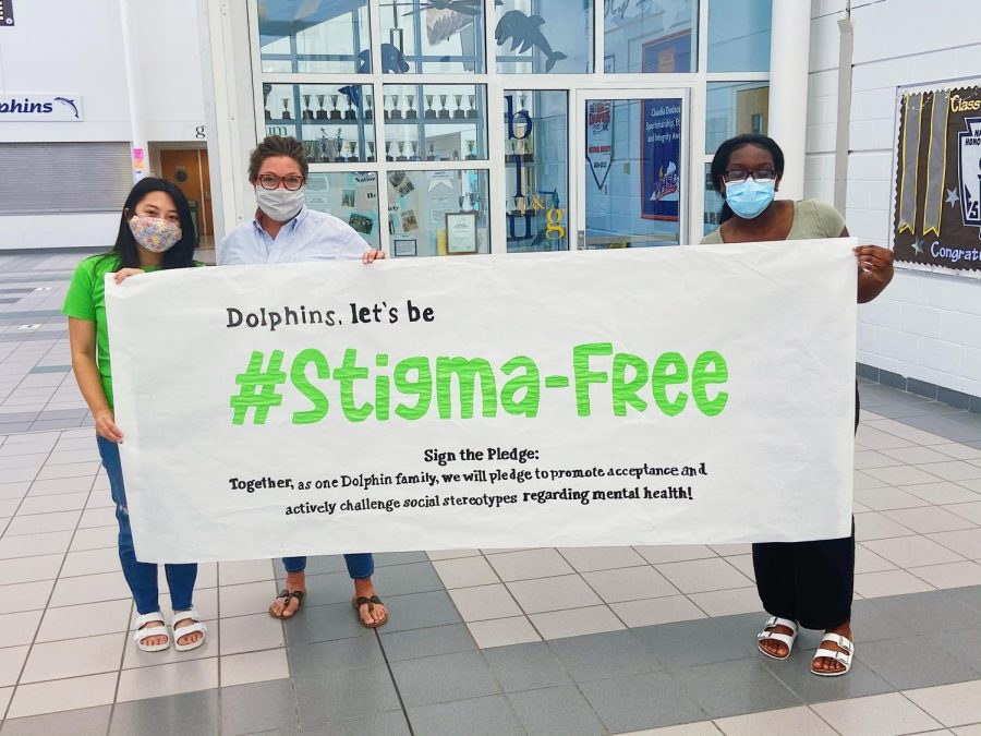 Club sponsor and school counselor Joanna Buonviri, Founder Nina Dao, and Co-President Chelsea Agyei hold up #EndTheStigma banner before it is hung near Counseling office on May 17.