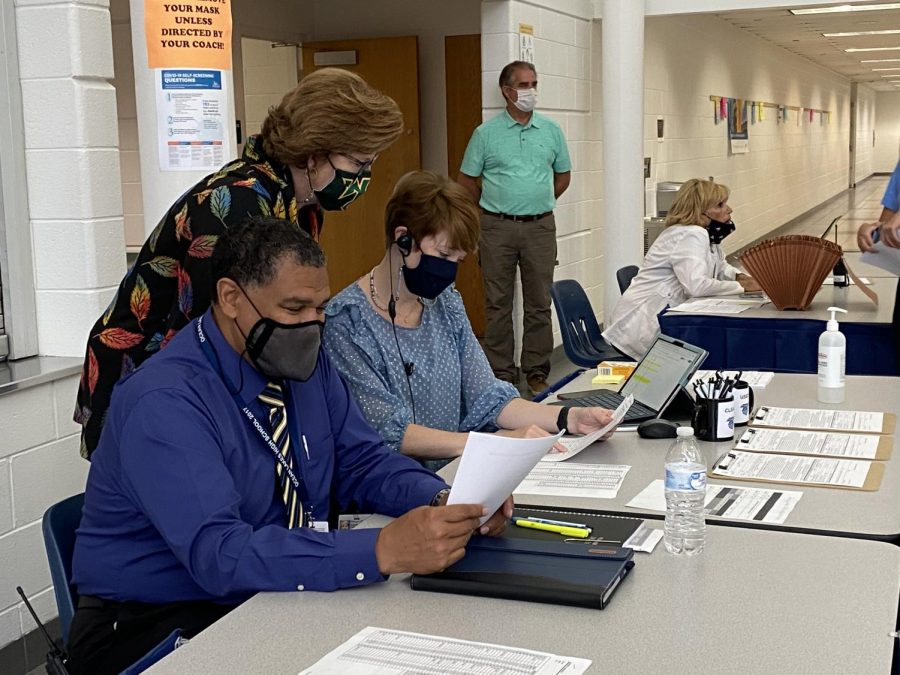 (From left to right) School administrators Steven Oberlander, Dr. Claire Leblanc, and Darcy Parker review papers regarding the first dose of the Pfizer vaccine. Picture taken May 25.