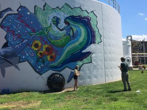 Nikki Boardman and her muralist mentor painting the mural on a water tank at the HRSD.