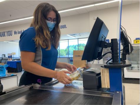 Senior Adriana Raimandi scans groceries at neighborhood food lion on Aug. 5.
